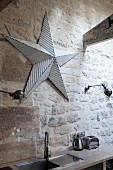 Sink in kitchen counter below metal star between retro sconce lamps on rustic stone wall