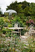 Ornate vintage metal chairs and table on stone floor in romantic garden with small orangery in background