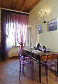 Mediterranean dining area with purple plexiglas chairs and accessories