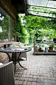 Garden table with metal base and mosaic top on roofed terrace with cobbled floor and outdoor kitchen in background