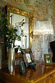 Designer lamp on chest of drawers below gilt-framed mirror on rough wall