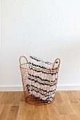Black and white cushion in copper-coloured wire basket