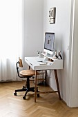 Computer on modern desk and vintage chair