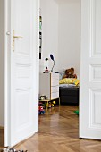 Open white double doors in period apartment with herringbone parquet floor and view into child's bedroom