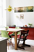 Green classic shell chairs and Tripp Trapp highchair around dining table below classic pendant lamp
