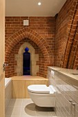 Bathroom with modern installations, brick wall and Gothic windows in converted church