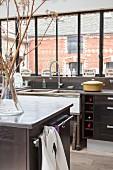 Küche im Industriestil mit Blick auf ein Backsteinhaus