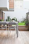 Tisch mit Stühlen auf Terrasse mit Holzboden im Hinterhof