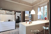 White kitchen counter below pendant lamps in open-plan kitchen