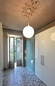 Spherical lamp suspended from painted ceiling above modern fitted cupboards with white glossy doors and glass sliding elements in traditional interior