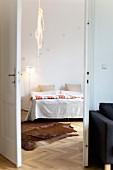 Cowhide rug and rope light in bedroom seen through open double doors