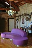 Geschwungenes violettes Designersofa auf Dielenboden unter Glas-Kronleuchter in Loftwohnung mit Industriecharme