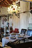 Tellerstapel und Terrine mit Deckel auf Tisch unter Kronleuchter in Loft-Wohnraum