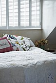Pale bedspread and embroidered cushions on bed below window with closed interior shutters