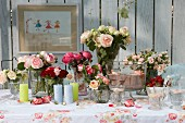 Summery buffet and various vases of roses on table
