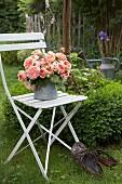 Strauß Rosen in Zinkkanne auf einem Gartenstuhl