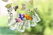 Eine Girlande mit Sommerblumen in Glasfläschchen und eine Papiergirlande für den Garten
