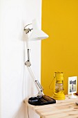 White desk lamp next to yellow storm lamp on wooden table in corner against yellow and white wall
