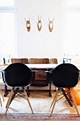 Black shell chairs around white table and retro cinema seats below three hunting trophies on wall