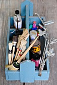Various paintbrushes, paints and painting utensils in wooden trug