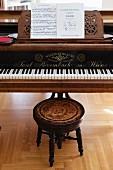 Klavierflügel mit Notenheft und antikem Hocker mit gedrechselten Beinen