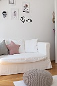 Row of scatter cushions on sofa with white loose cover below framed drawings and wall stickers