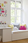 White desk below colourful children's drawings on wall and next to window seat with seat cushion and bright scatter cushions