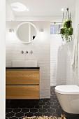 weiße Backsteinwand im Bad mit schwarzen Wabenfliesen am Boden
