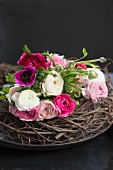 Bouquet of pink and white ranunculus and anemones on twig wreath