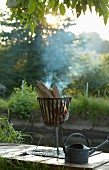 Fire in fire basket and vintage zinc watering can outdoors