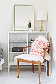 Cushion and sheepskin on antique armchair in corner in front of white cabinet with mirror and table lamp on top