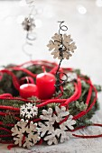 Wreath decorated with wooden snowflakes and red cord