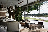 Sofa landscape and hanging lounger on covered terrace, river view
