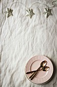 Star.shaped fairy lights, plates and spoon on fabric surface