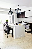 White kitchen island with black bar stools under lantern lights in front of kitchen counter and open patio doors