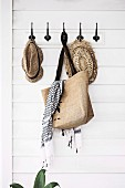 Vintage hook bar with straw hats and shopping bag on white wooden paneling