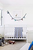 Bright children's room with white crib, toys and pennant chain as wall decoration