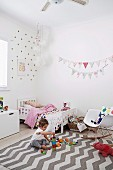 Bright girl's room with fabric pennant chain and playing girl on carpet