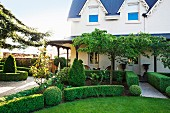 Formgeschnittene Hecken vor elegantem Landhaus mit umlaufendem Vordach