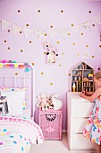 Girl in pink children's room with dotted wall