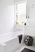 White bathroom with tub under the window