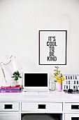 Black-framed saying above a desk with a laptop