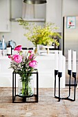 Bouquet in glass vase with metal frame and black metal candle holder