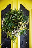 Wreath of different branches on a yellow front door