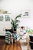 Rattan armchair with knitted blanket and dog in front of sofa with young person lying in living room