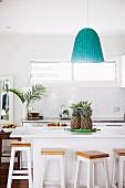 Barhocker aus Holz um weisse Küchentheke mit Ananas, darüber Pendelleuchte mit türkis Lampenschirm