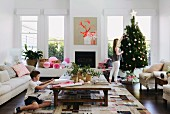 Teenagers decorate Christmas tree and boy wraps Christmas present in contemporary Australian home decor