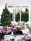 Australian living room with decorated Christmas tree, wrapped gifts and cozy upholstered armchair