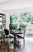 Dining area with vintage Rococo style chairs in front of window, antique mosaic parquet