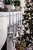 Christmas decorations in silver with a blue ribbon on a mantelpiece